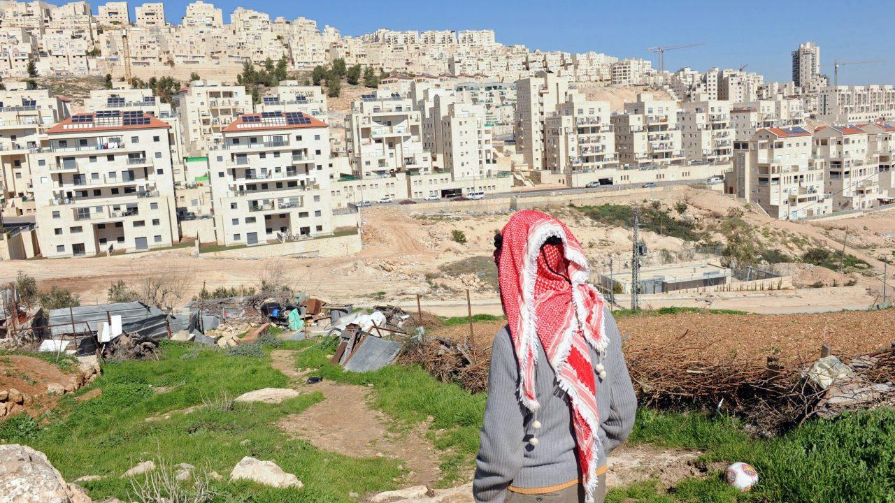 فلسطيني يقف على أرضه المطلة على مستوطنة هار حوما الإسرائيلية في الضفة.
