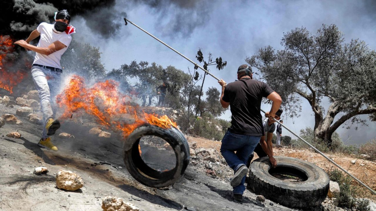 Palestinian protesters set tires aflame during clashes with Israeli security forcesf following a demonstration in the village of Beita, south of Nablus, in the occupied West Bank on June 11, 2021.  / AFP / JAAFAR ASHTIYEH