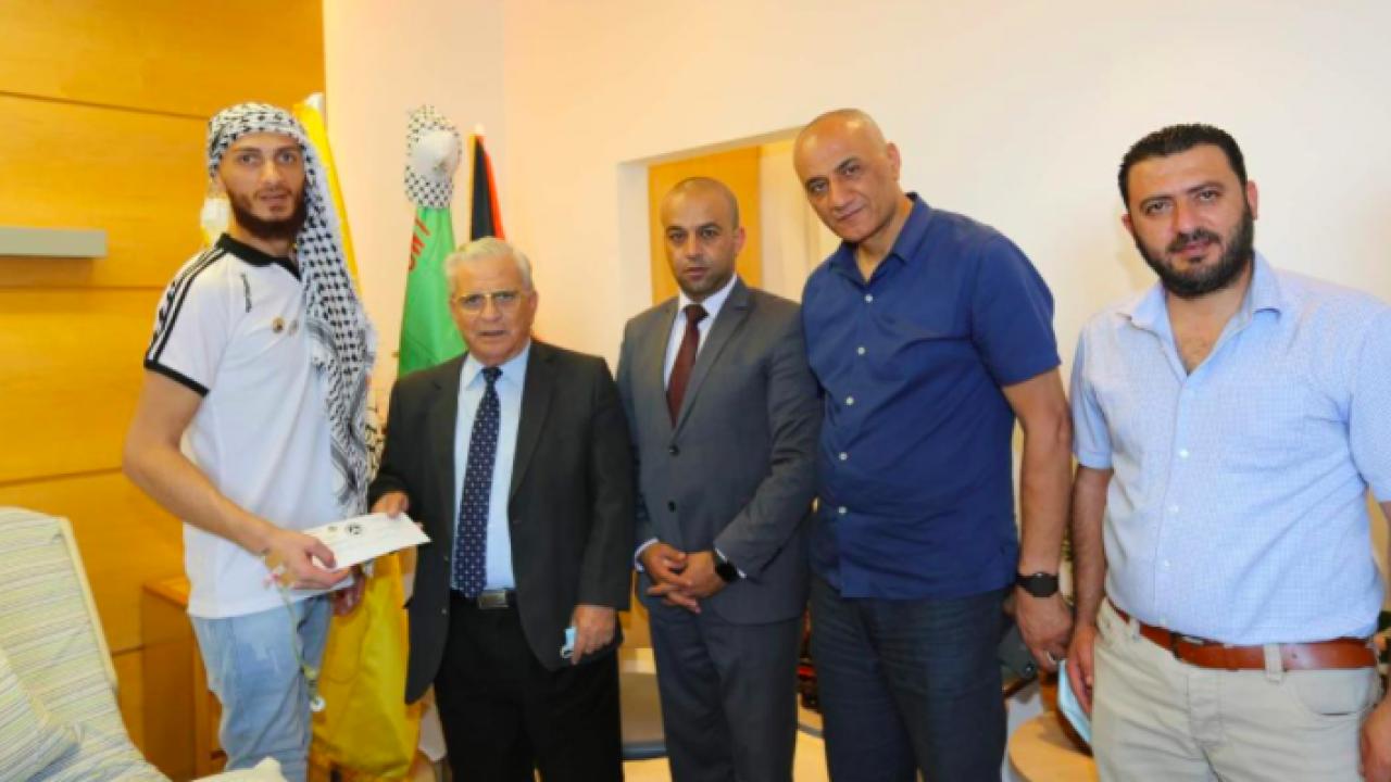 رئيس جامعة القدس المفتوحة يونس عمرو خلال تسليمه الأسير المحرر الغضنفر أبو عطوان منحة دراسية