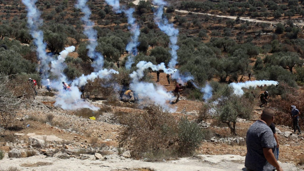 (210709) -- NABLUS, July 9, 2021 (Xinhua) -- Protesters run to take cover from tear gas canisters fired by Israeli soldiers and members of Israeli border police during clashes following a protest against the expanding of Jewish settlements in the village of Beita, south of the West Bank city of Nablus, July 9, 2021. (Photo by Nidal Eshtayeh/Xinhua)